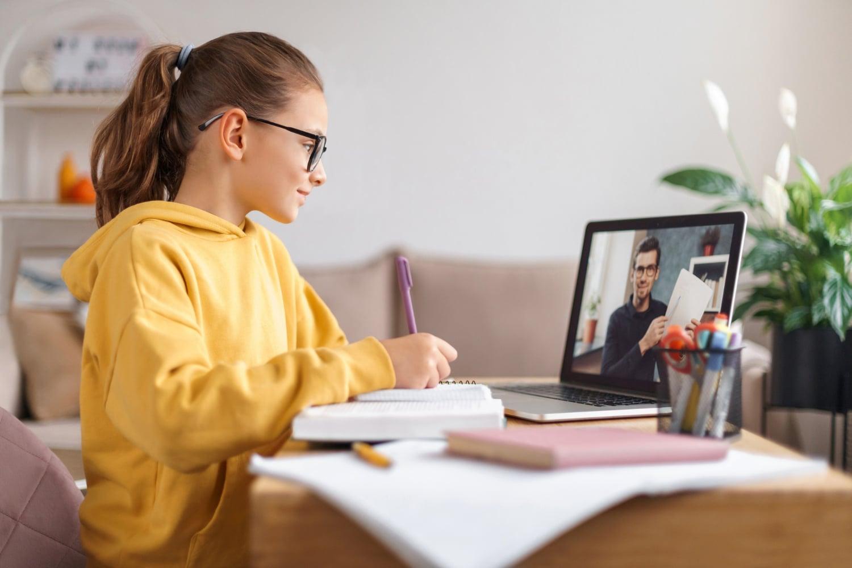 School girl wearing glasses using laptop